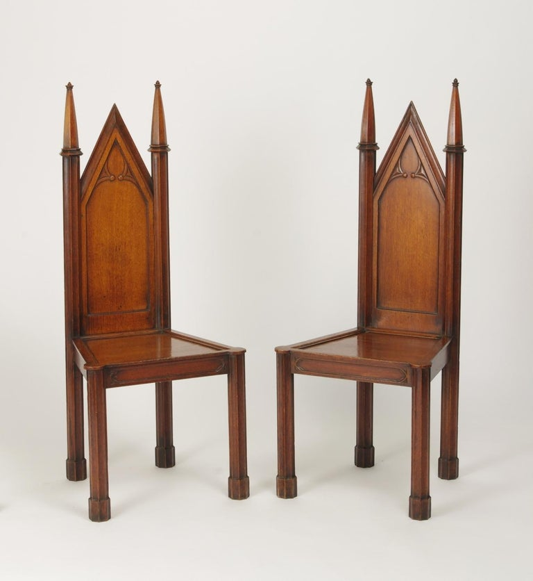 Pair of George III oak gothic hall chairs, each with a gabled back with gothic tracery between fluted spires, the plank seat with a molded edge on an apron with similar tracery and raised on fluted legs with plinth feet.