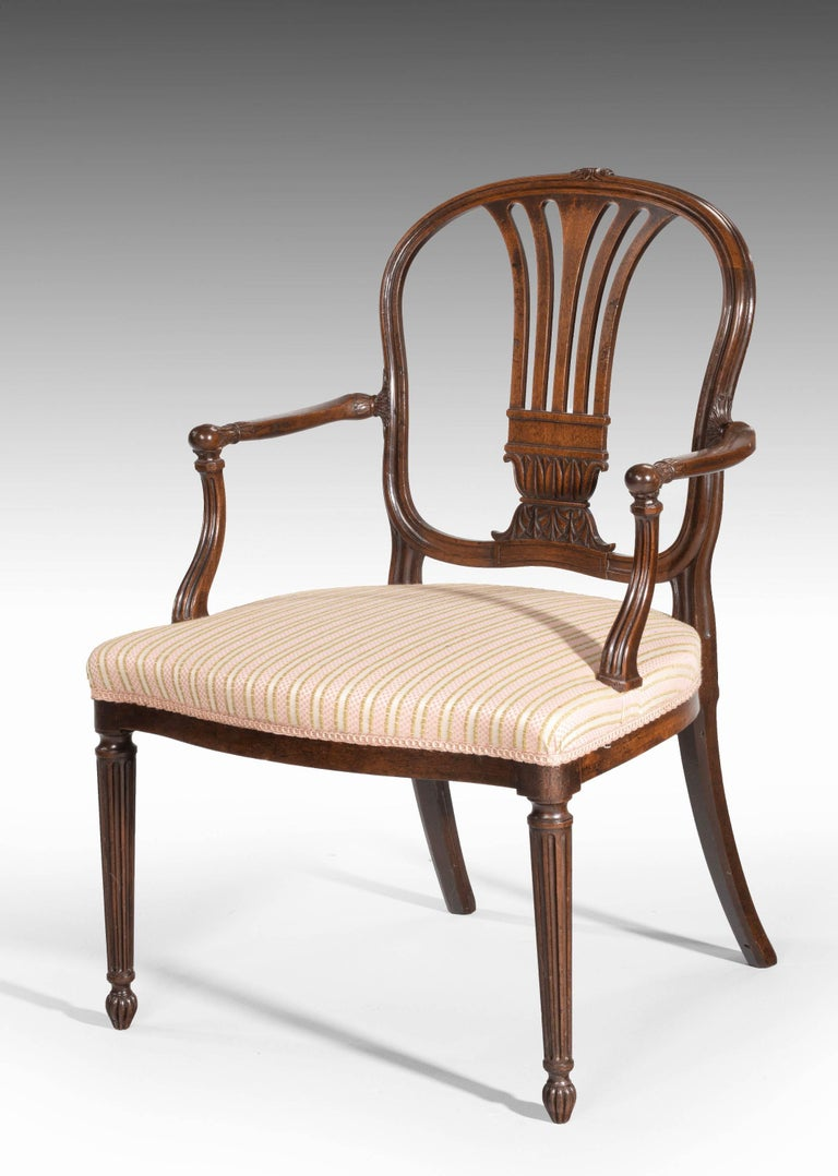 A fine pair of George III period mahogany elbow chairs by Robert Manwaring. The termini on the supports and arms of typical ball construction. Very well carved detail to the pierced back splats the sinuously shaped sections to the back are very well