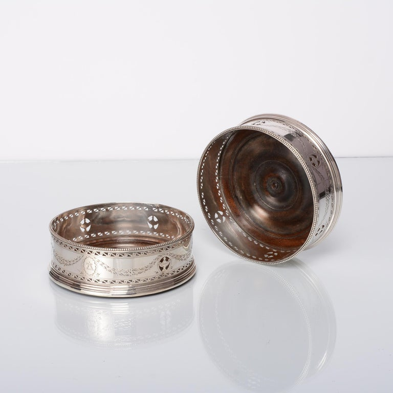Pair of George III silver wine coasters with pierced and engraved neoclassical pierced and engraved decoration and fine beaded borders. This attractive pair has its original turned wooden bases.  Neoclassicism is the 18th and 19th century movement