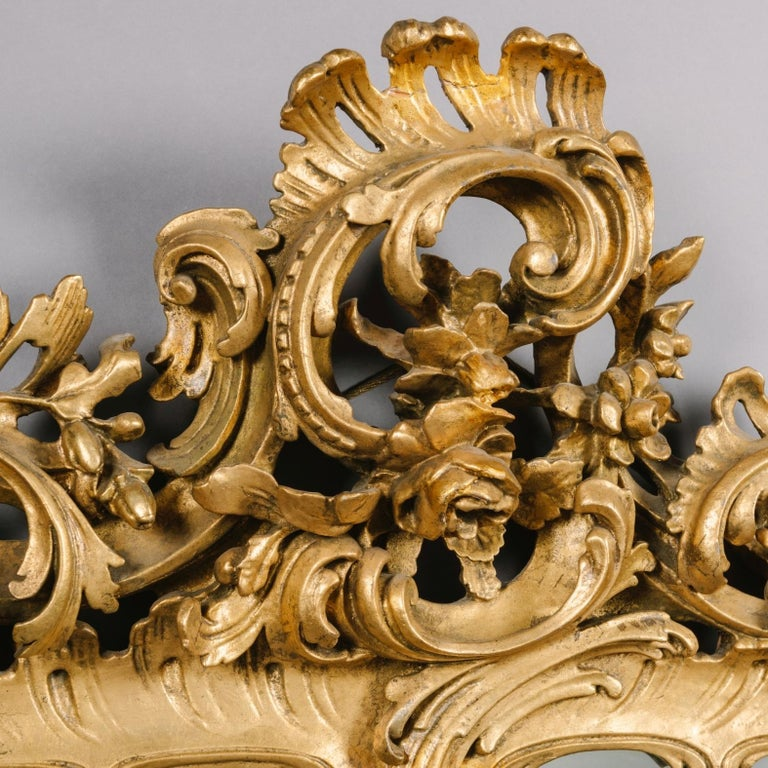 A fine pair of George III style carved giltwood mirrors.  Each mirror has a rectangular bevelled mirror plate within a carved giltwood frame of acanthus and 'C'-scrolls, surmounted by a pierced scrolling cresting of acanthus, oak leaves and