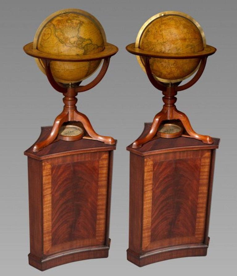 Each with brass meridian within rings applied with printed zodiac scales, raised on mahogany stands with curved brackets on ring turned columns and splayed tripod supports and pad feet joined by a stretcher centered by a compass. The terrestrial