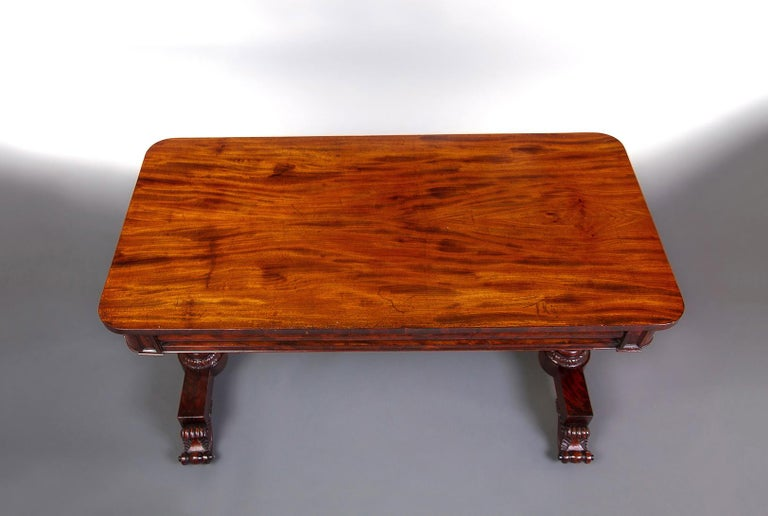 The highly figured tops above a convex frieze on a highly decorative trestle base on brass casters. The carving to these tables is particularly good.