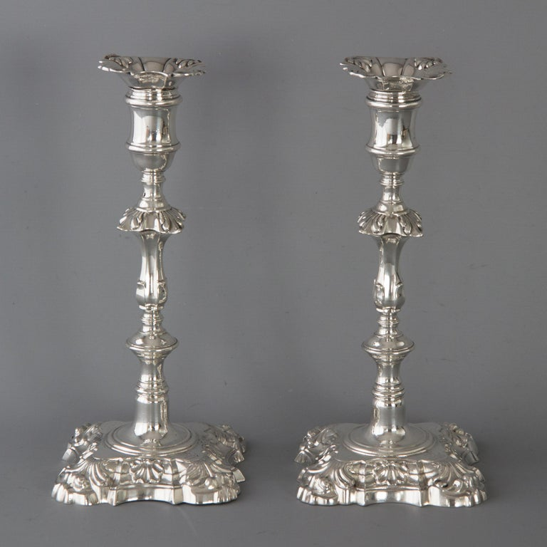 A very good pair of George III cast silver table candlesticks of shell and scroll decoration to a square shaped base. The stem with a circular knop and a fluted rectangular knop. Rope twist decoration to the base and capitals. Conforming shell