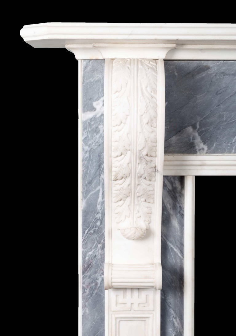 A pair of antique dove grey and white statuary marble fireplaces from the late Gerogian period. The long elegant acanthus carved corbels with recessed pilasters below, support a moulded and chamfered edge mantelpiece. The exquisitely carved centre