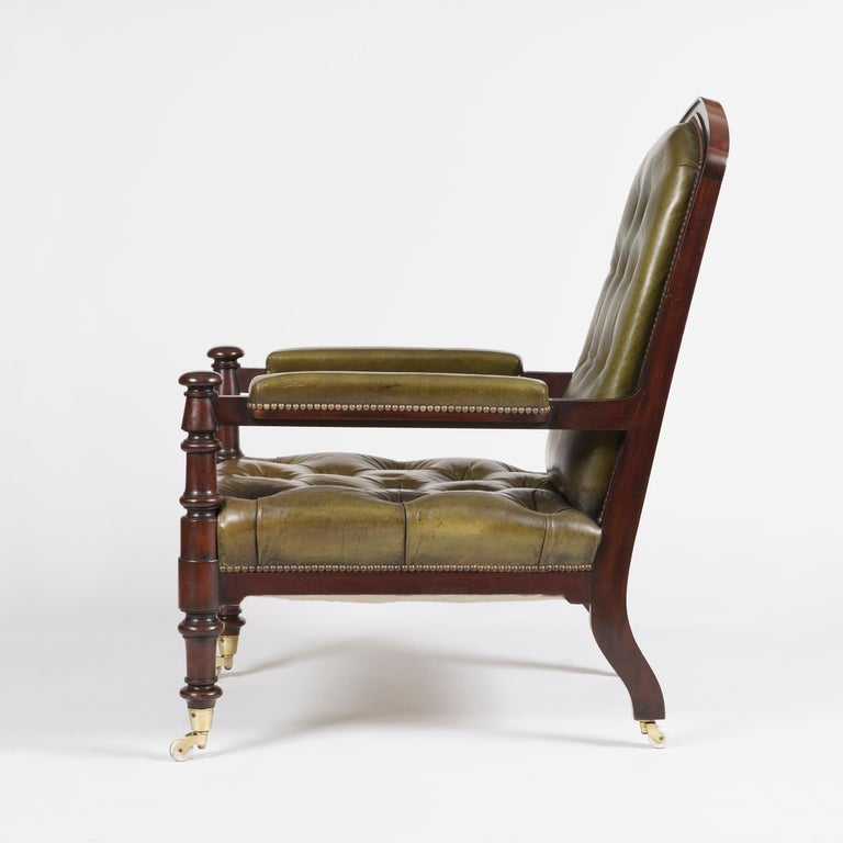 A good pair of library armchairs of the late Georgian period  Constructed in mahogany, and rising from ring turned columnar legs terminating in porcelain castors; the upholstered arms conjoin with the arched panelled backs, being upholstered in