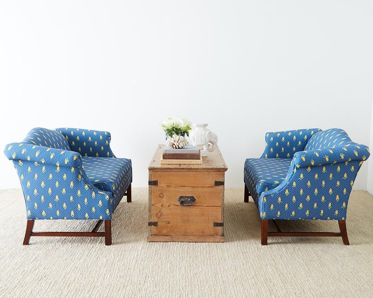 Pleasing pair of mahogany framed camelback settees or love seats made in the George III style. Featuring a yellow tulip motif fabric over a cobalt blue ground. Bespoke pair of settees from the San Francisco Design Center. The mahogany frames made in