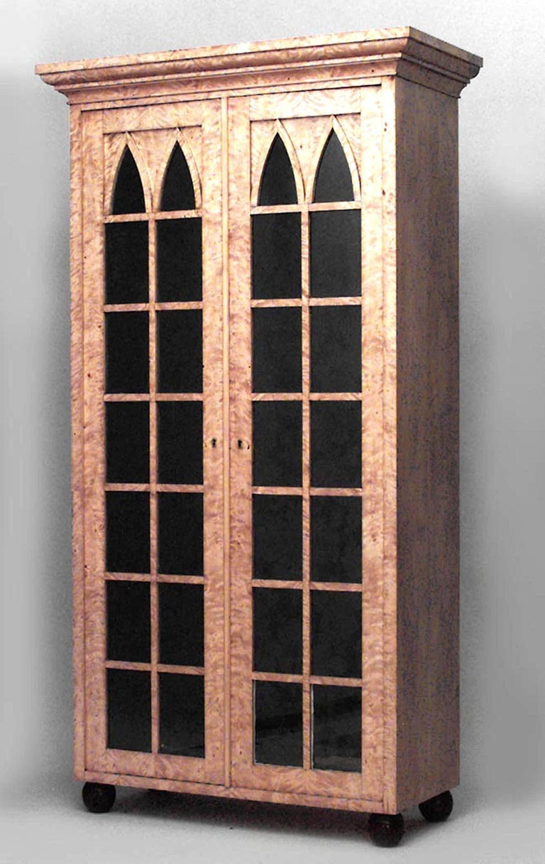 Pair of German Biedermeier (19th Century) flame birch Gothic arch design two-door bookcase cabinets on black lacquered claw feet.