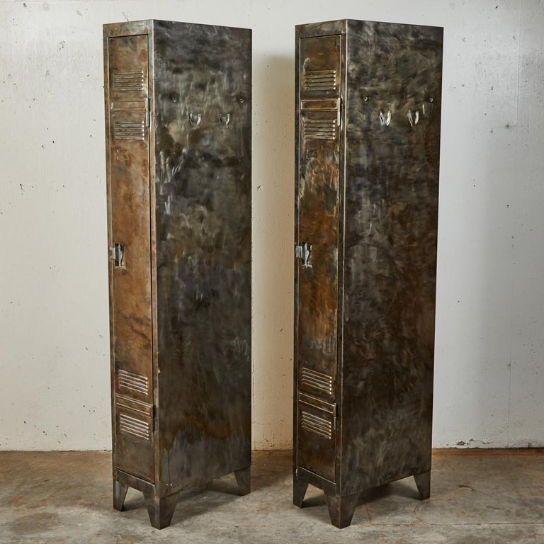 A pair of tall narrow lockers with upper and lower vents, latch locks and angle cut feet.