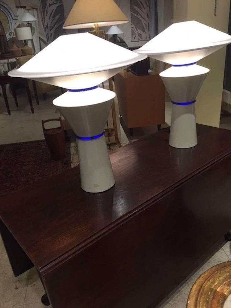Pair of Graphic modern brilliant white lamps created by Arteluce, Designed by Giuseppe Ramella Each lamp has an individual double socket illuminating top and base Blue transparent detail on base Created in Milan, circa 1980.