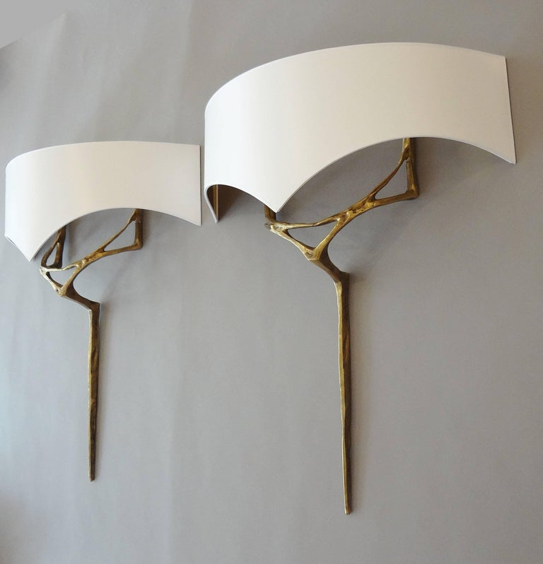 Félix Agostini (1910-1980) Pair of gilt bronze sculpted wall-sconces called Erato, with a white card shade, gilt inside. Measures: Bronze height 58 x width 5 x depth 10 cm. Shade height 20 x length 52 x depth 19 cm.3
