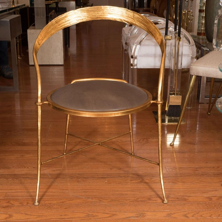 Pair of gilt metal, sculptural chairs with upholstered seats.