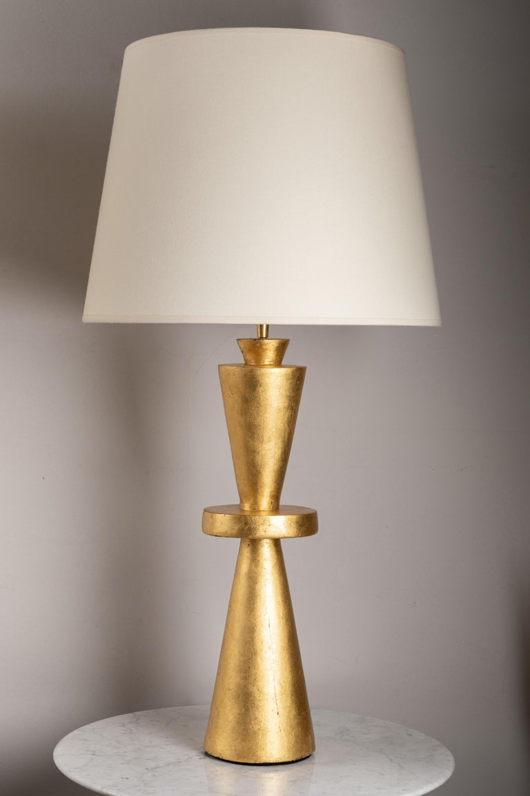 Pair of plaster lamps.  Hand gilded with 22 carat gold leave  With custom made shades. France, contemporary creation Wired for Europe.  Measures:  Total height : 86.5cm - 34 inches Plaster base height : 52.5 cm - 20.7 inches Diameter