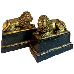 Pair of Gilt Reclining Lions on Black Stands
