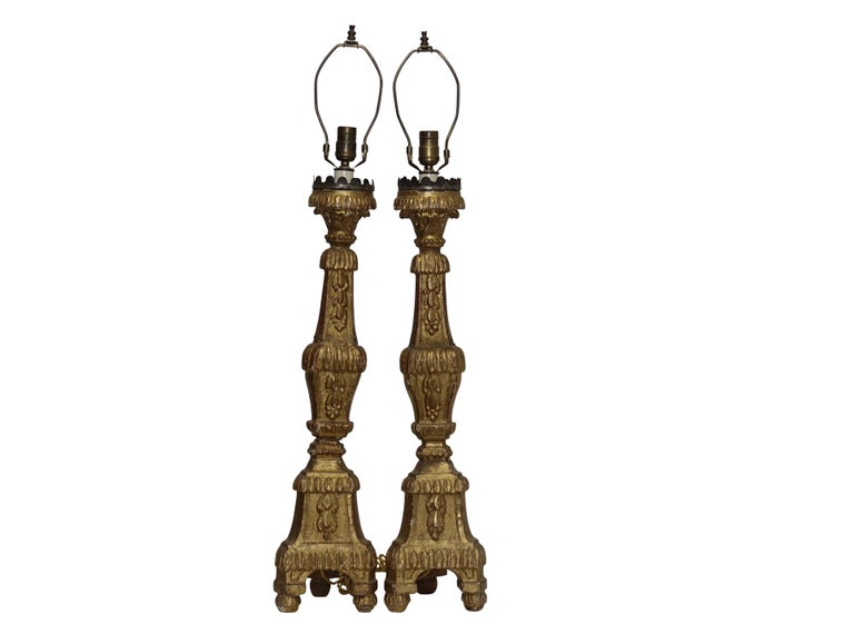 A pair of carved and giltwood altar candle sticks with tin cups having a scallop rim, now electrified as lamps. Recently re-wired. Italy, 18th century. Height measurement to the top of the socket is 31 inches.