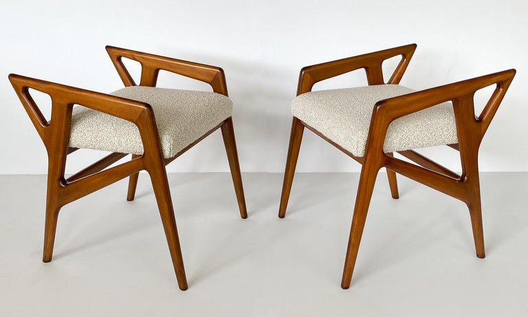 Pair of sculptural carved solid Italian walnut stools by Gio Ponti, circa 1950s. Newly upholstered in a two-toned taupe and cream textural bouclé fabric by Pierre Frey. Angular walnut frames are newly refinished. New cushions. A fabric swatch is