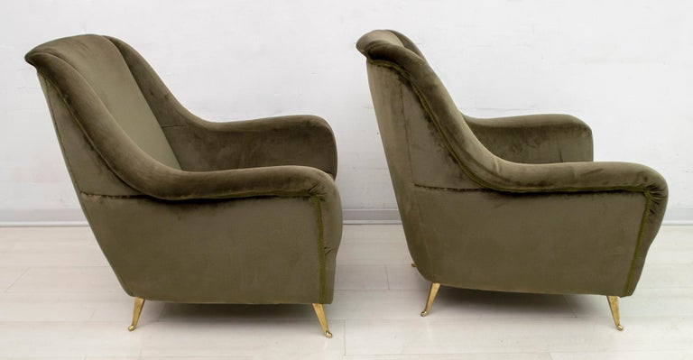 Elegant and splendid pair of Mid-Century Modern armchairs with high back and brass feet, attributed to Gio Ponti, 1950 for ISA Editions, Bergamo. Sculpted profile, refined lines, sensual and deep comfort. The chairs have their original dark green