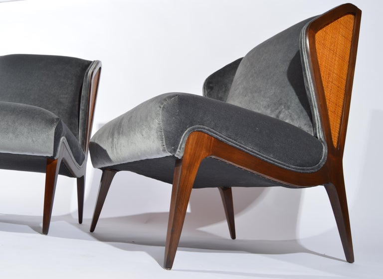 A pair of 1950s walnut cane embellished wingback slipper chairs in the manner of Gio Ponti having fresh gray velvet upholstery and cushioning.