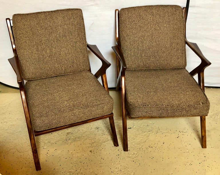 Pair of Mid-Century Modern rosewood or walnut armchairs having both been Reupholstered and fully Refinished in the style of Gio Ponti. These simply sleek and stylish chairs depict the Mid-Century Modern craze it its finest form. One of six pairs