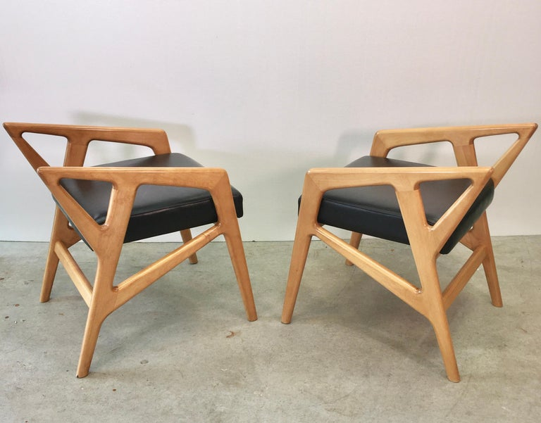 Pair of Gio Ponti style sculptural stools with newly upholstered black faux leather seats. According to the Gio Ponti Archives the original design of these stools was Based Upon the model 687 chair for Cassina in 1953. One can also observe the