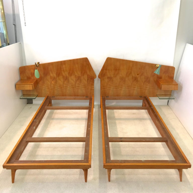 1950s Italian pair of twin beds in light color finished birch wood with highly figural book matched birch veneer asymmetric headboards mounted with floating nightstands with a single drawer having stylish angled drawer face and floating glass shelf