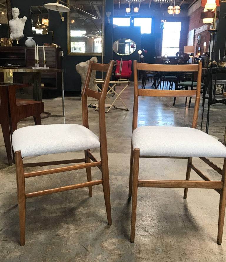 Pair of iconic Gio Ponti Superleggera dining chairs with upholstered fabric.