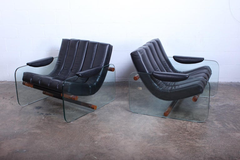 A pair of glass sided lounge chairs by Mirox with original black vinyl upholstery.