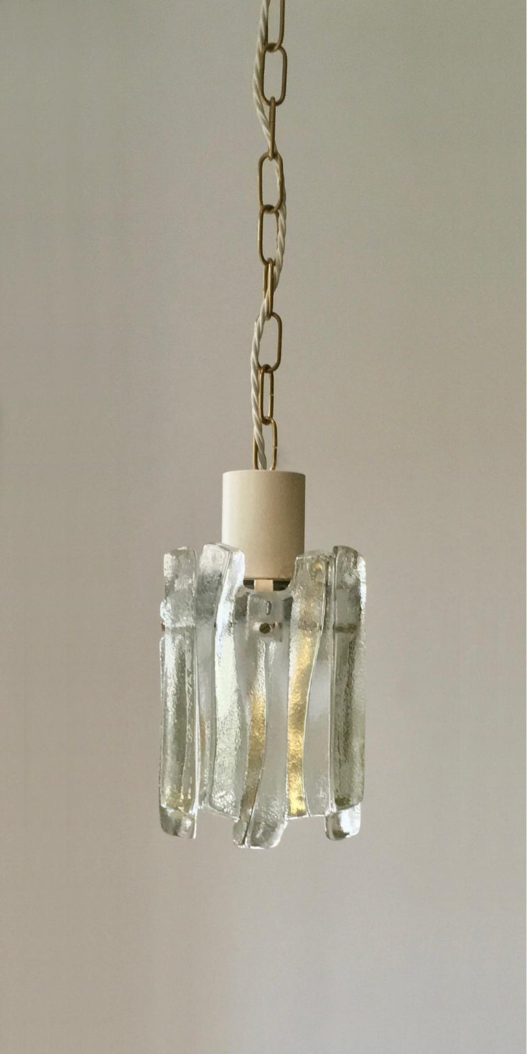 A pair of glass pendant lights by Kalmar of Austria, late 1960s or early 1970s design. Two pairs available; price per pair.  Simple but stylish lights giving a nice diffuse light: each fixture comprises four glass panels of heavy, textured glass