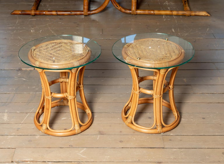 Pair of glass top rattan and woven wick tables with brass details.