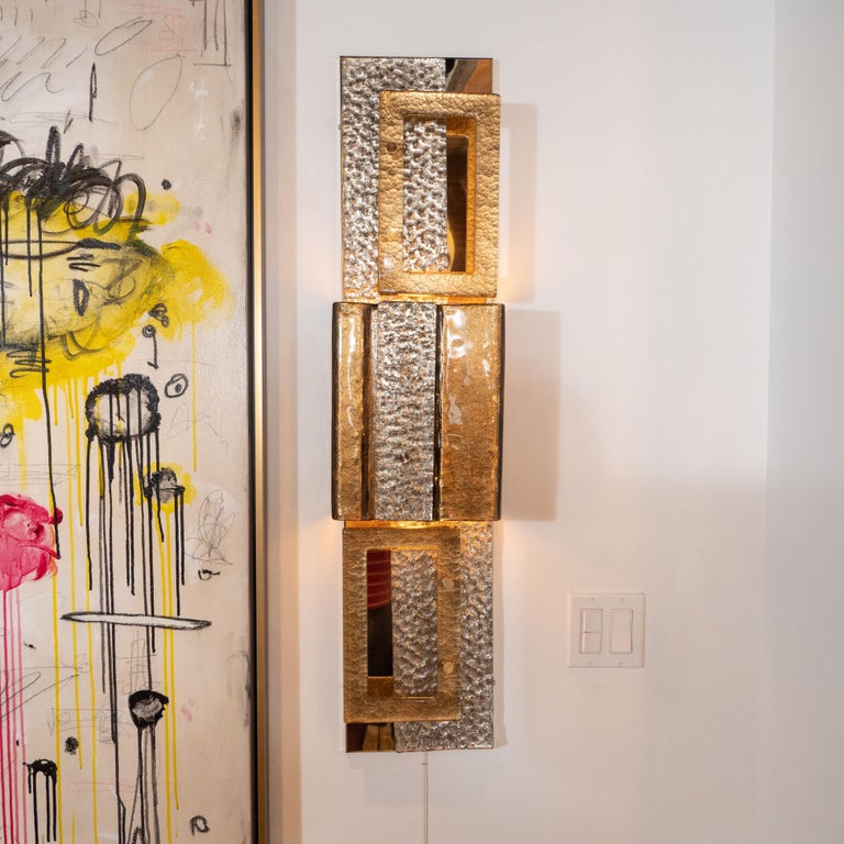 This impressively large pair of gold and bronze Murano glass and brass sconces consists of three multi-stacked shimmering gold and bronze colored and textured glass and natural polished brass elements in various rectangular shapes. Light is casted