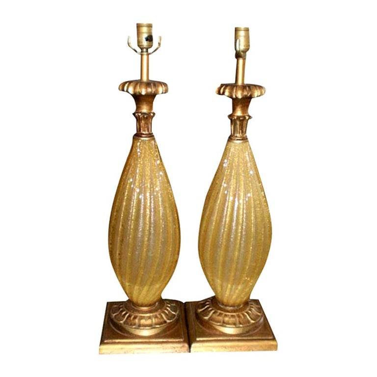 Gorgeous pair of vintage Murano glass lamps, gold with gold flecks on giltwood bases. This pair of Venetian glass lamps are in the style of Barovier. For a more modern look, these the bases on these Hollywood Regency Murano glass lamps could be