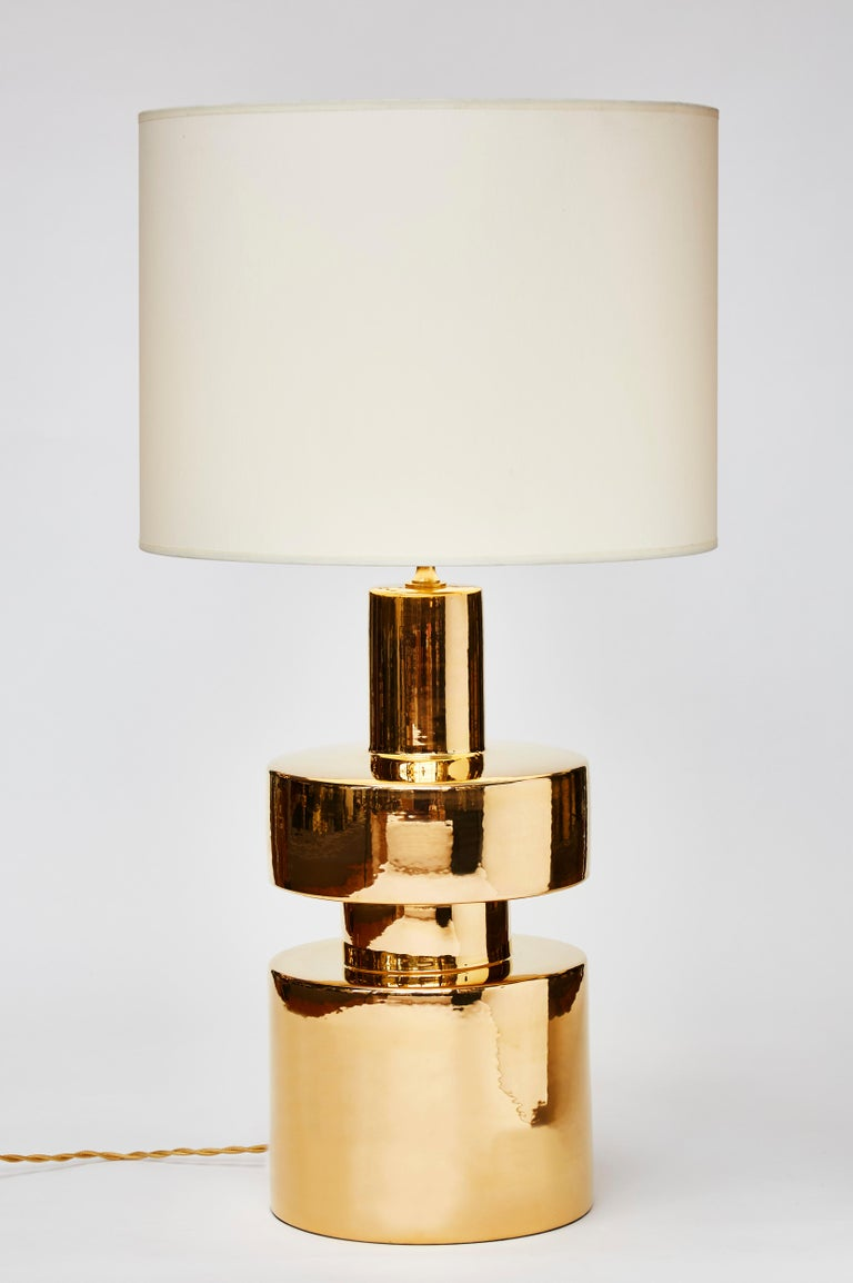 Pair of cylindrical table lamps made of ceramic covered with a golden glaze reflecting the light.