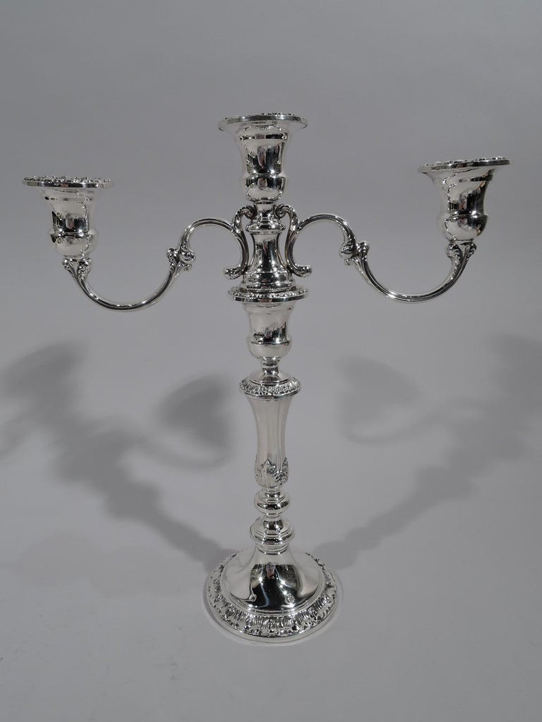 Pair of Classical 3-light sterling silver candelabra. Made by Gorham in Providence. Each: Tapering and knopped shaft with acanthus leaves on domed foot. Central light on spread base mounted with two scrolled arms, each terminating in single socket.