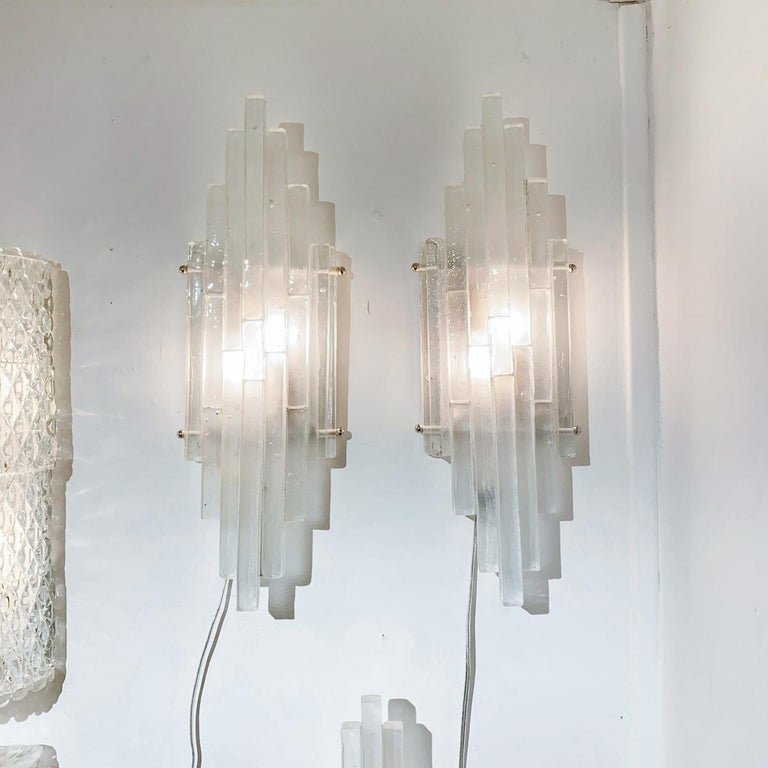 Sconces composed of clustered frosted glass strips in a graduated arrangement by Poliarte.