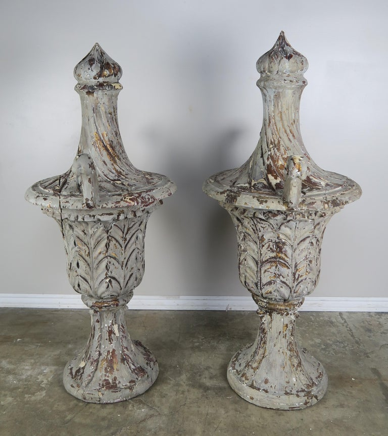 Pair of grand size carved wood flamed finial urns with two arms. The urns have a beautiful worn grey painted finish with natural wood exposed underneath the distressed paint.