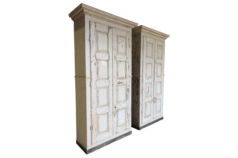 A very handsome pair of grand scale armoires from the Veneto region of Italy. Soundly constructed from painted wood with molded door panels and interior shelves and drawers. Excellent storage capacity.