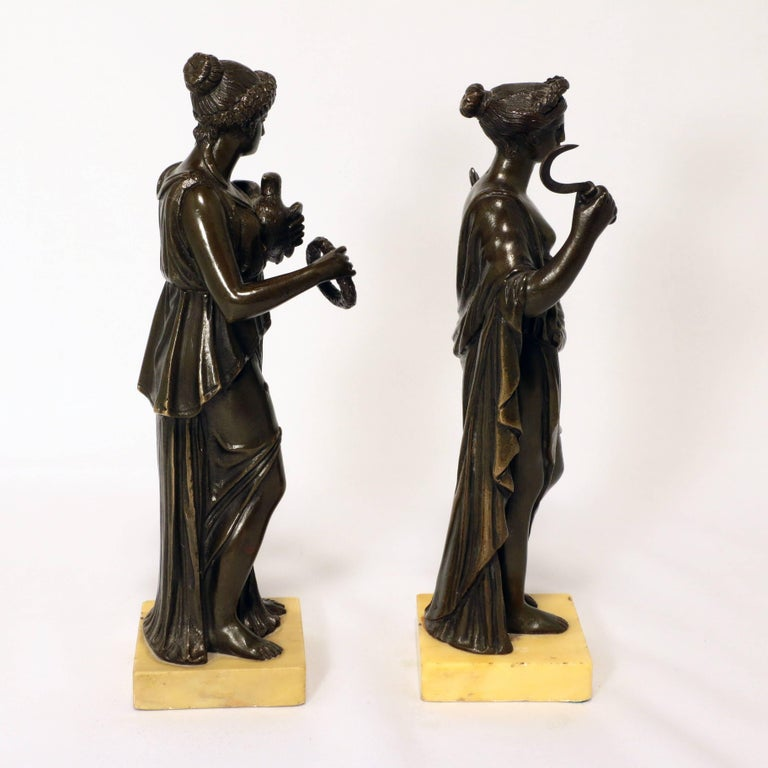 This striking pair, one of Ceres, emblematic of the harvest, the other with a dove and laurel wreath are well modelled as elegant figures in flowing gowns. Each is presented on a square pale ochre marble base.