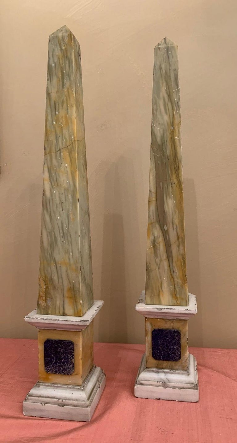 A pair of late 19th century Grand Tour Obelisks. The mouldings in Carara, the plint in Sienna, the plaque in Lapis Lazuli and the obelisks themselves in onyx.