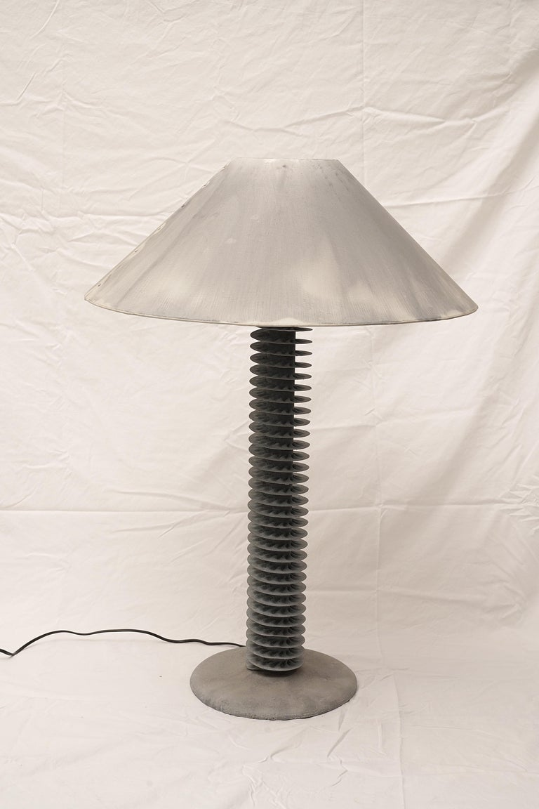 An unusual re-purposing, spiral grey metal water condensers mounted on a cast stone base and stem to make a great pair of table lamps. Gray metal lamp shades with intentional but subtle color variations. American, circa 2000. Shades are 24