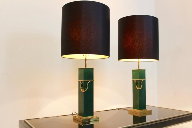 Sophisticated pair of midcentury table lamps from the 1970s. The square brass bases combined with the classical look in green give these lamps their modern and sophisticated form. The set features new black circular shades which give a very warm