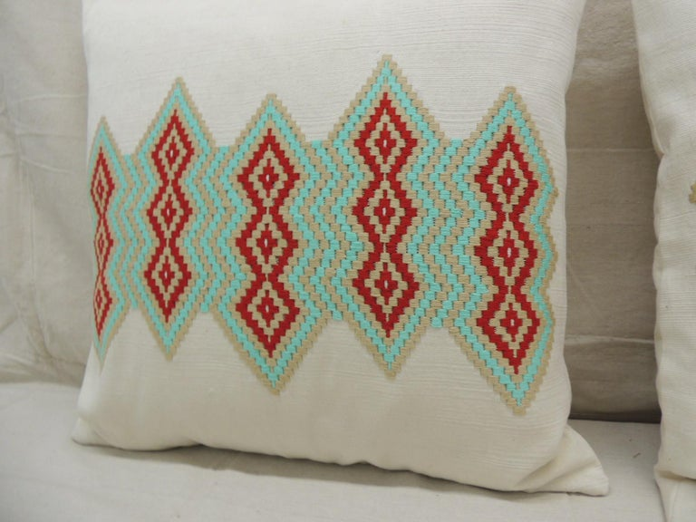 Pair of green and red embroidered square decorative pillows.