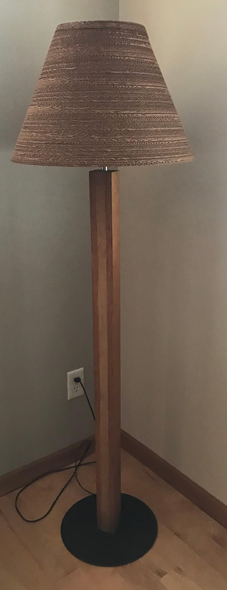 A pair of corrugated conical shade floor lamps with wood column bodies and brown iron disc bases. Often attributed to the architect, Frank Gehry.