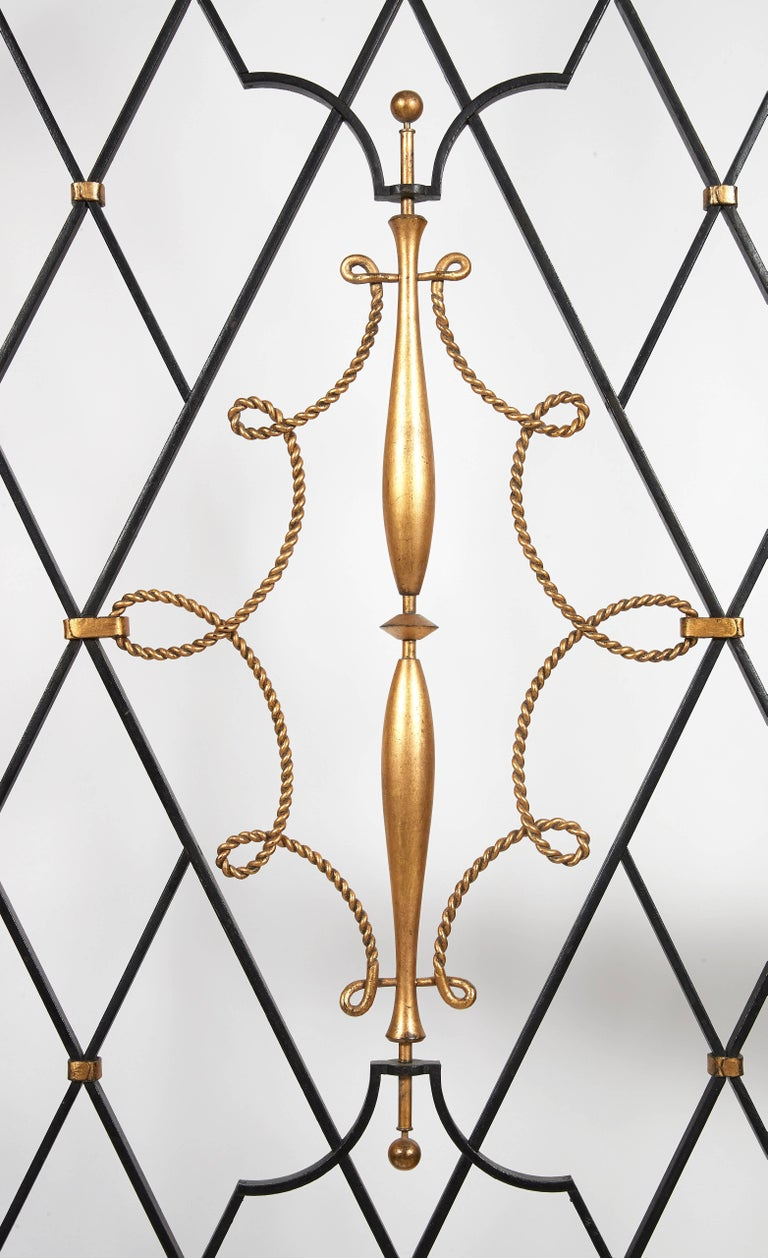 Pair of grids and their frames in black lacquered batted iron, forming an arc of a circle at the upper part, decoration of large openwork crosspieces, gilded metal spindles and ropes in center.  Bibliography : François Baudot,