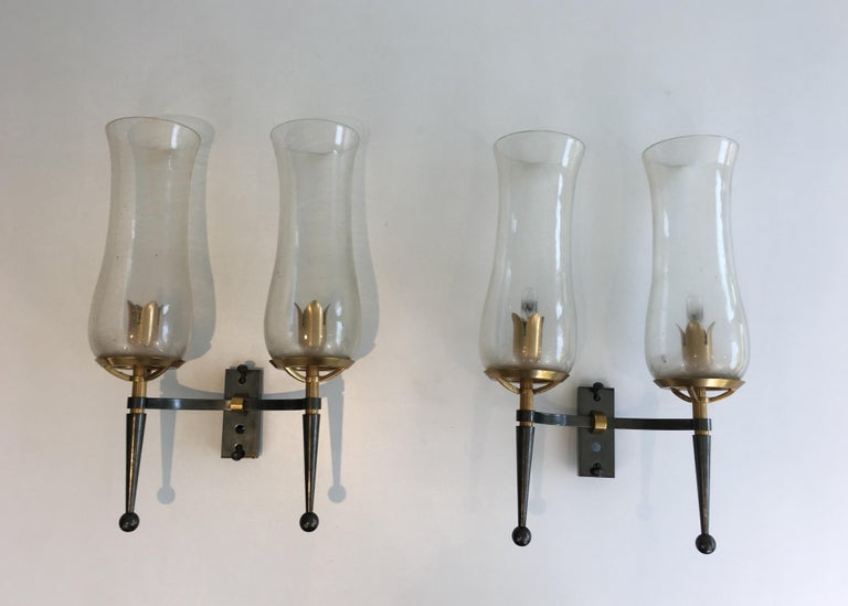 This beautiful pair of wall lights is made of gun metal steel and gilt bronze and brass. These wall sconces have very nice champagne Murano glass reflectors. They are probably a combination of a French designer and an Italian glass maker. Very nice