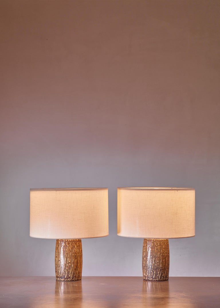 A pair of polychrome ceramic table lamps by Gunnar Nylund for Rörstrand, Sweden. The lamps have a slightly different but matching colorpattern in natural earth tones. Marked by Nylund and Rörstrand and in an excellent condition.  The measurements