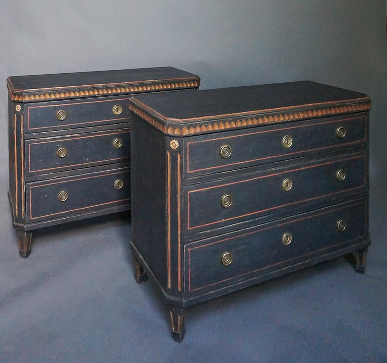 Pair of black three-drawer chests, Sweden circa 1880, in the Gustavian style. Shaped tops with lamb's tongue molding, canted and reeded corner posts, and tapering, reeded feet. Brass pulls and escutcheons.