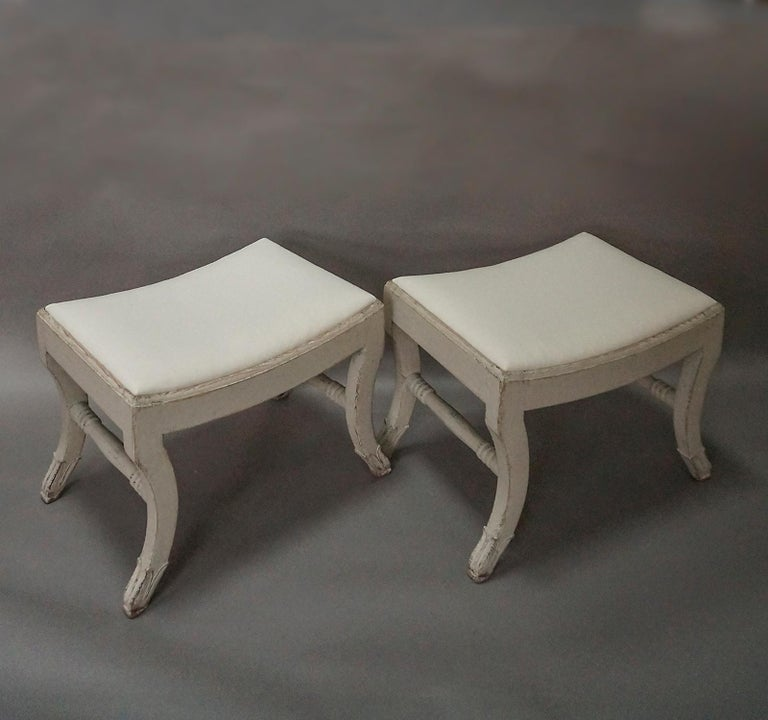 Pair of Swedish stools in the Gustavian style, circa 1910. Modified saber legs with acanthus leaf carving and turned stretchers. Slip seats and new tufted cushions.
