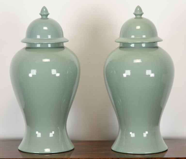 A classical pair of Celadon Ginger Jars by Haeger, USA, 1980s. The ginger jars are in very good condition. One lid has a small chip to the interior edge, as shown in images. The bottom of the jars has been predrilled and can be made into table