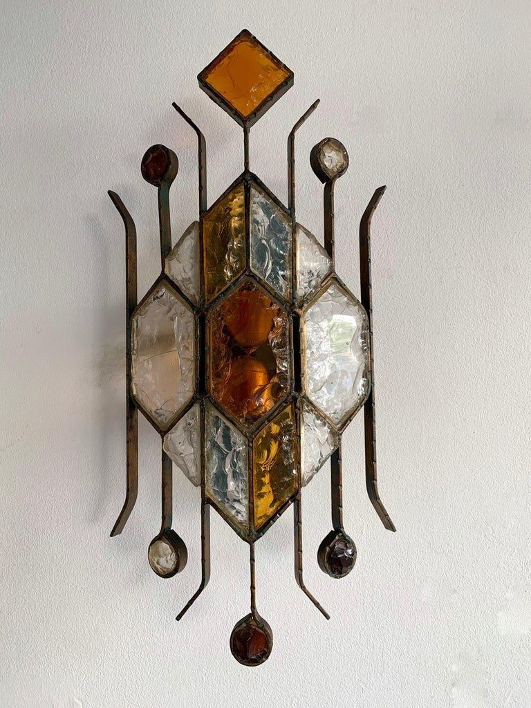 Pair of wall lamps lights sconces hammered glass and gilded patina wrought iron by the manufacture Longobard in Verona in a Brutalist style, the concurrent of Biancardi Jordan Arte and Poliarte during the 1970s. Nice combination of glass amber and