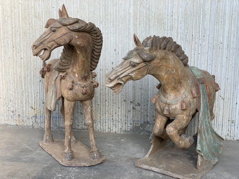 A one piece pottery horse, standing on all fours and striding with its right hoof forward. Extended snout ends in parted lips showing teeth beneath in a braying attitude. Low relief bridle on face and well defined eyes. Raised mane down back of the