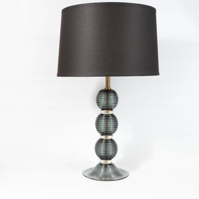 This refined pair of table lamps were realized in Murano, Italy- the islands off the coast of Venice that have been renowned for centuries for their superlative glass production. They feature three orbital forms in semi-opaque smoked graphite glass